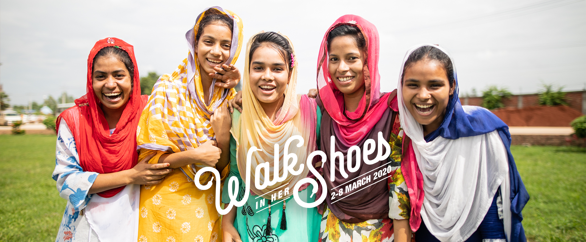 Walk in her Shoes logo. Image of girls laughing.